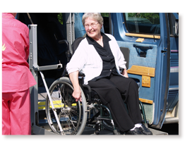 older woman in wheelchair coming out of lift van