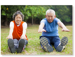 older man and woman on grass stretching/exercising